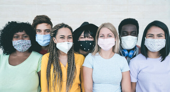 Young multiracial people wearing protective masks during coronavirus outbreak - Social distance between friends concept - Main focus on girl with yellow t-shirt face