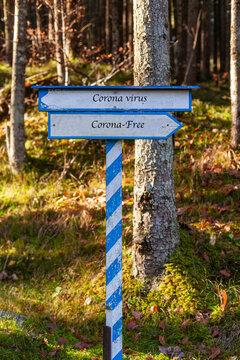Weiß-Blaues Hinweisschild,  Richtung Corona-Virus oder Corona Frei in Englischer Sprache