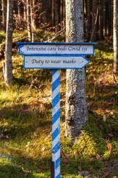 Weiß-Blaues Hinweisschild in welche Richtung es gehen soll. Maskenpflicht oder Intensivbetten. Beschriftung in Englischer sprache