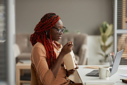 Side view portrait of young African-American woman eating takeout lunch and looking at laptop screen while enjoying work form home office, copy space