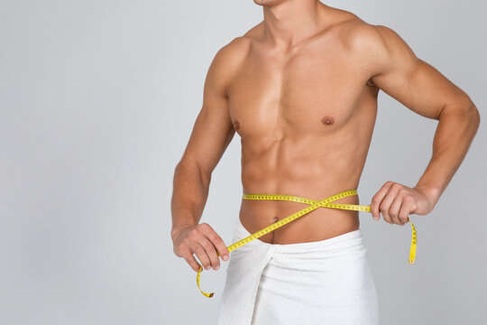 Muscular man measuring his waist with yellow tape