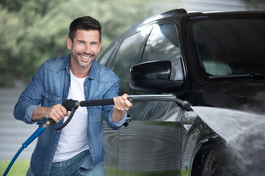 water spray gun held by a man to wash car