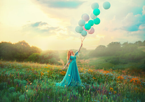 Happy woman walks in blooming valley. Fantasy girl princess holding in hand ball air balloon. long blue tulle fashion dress. Sunset sky magic haze fog, flowers green meadow. blonde hair. Smiling face
