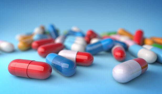 Close up of assorted capsules on blue background, 3d illustration. Concept image for pharmaceutical industry and medication research.