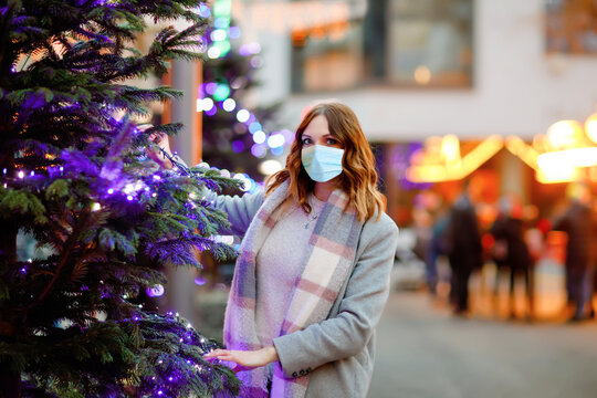Woman with medical mask on German Christmas market. People with masks as protection against corona virus. Covid pandemic time in Europe and in the world