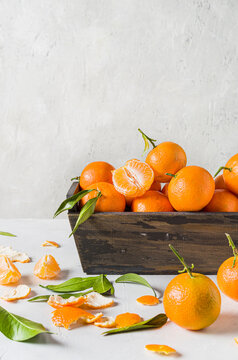 Tangerines, mandarins, clementines, with leaves in wooden box. Front  view. Space for text