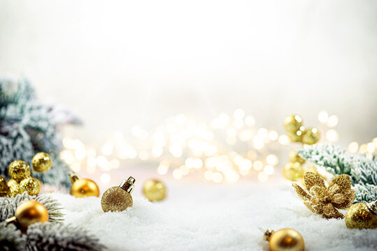 Christmas gold decorations on snow with fir tree branches and christmas lights. Winter Decoration Background