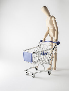 still life with wooden mannequin and shopping trolley