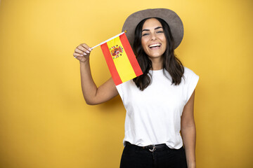 Beautiful woman wearing casual white t-shirt and a hat standing over yellow background holding the...