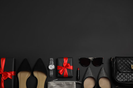 Gift boxes, shoes and stylish women's accessories on black background, flat lay. Space for text