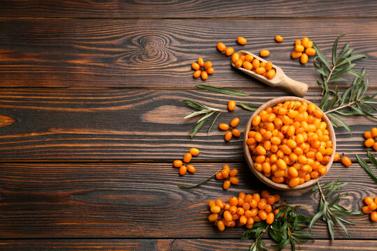 Fresh ripe sea buckthorn on wooden table, flat lay. Space for text