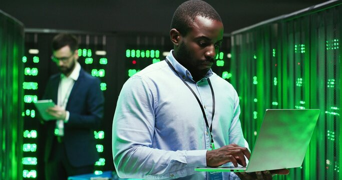 Portrait of handsome African American young man cryptograph standing in big data storage and working as typing on laptop computer. Male Caucasian analytic on background. Information security concept.