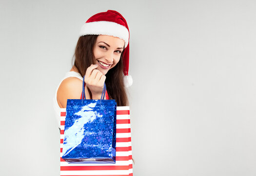 Happy laughing woman in Santa Claus hat holding Christmas present packages. Portrait