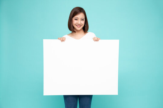 Young asian woman showing and holding blank white billboard isolated on green background
