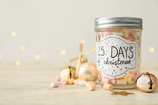 Glass jar with label 25 Days of Christmas and tasty marshmallows on white wooden table against blurred background, space for text. Advent calendar