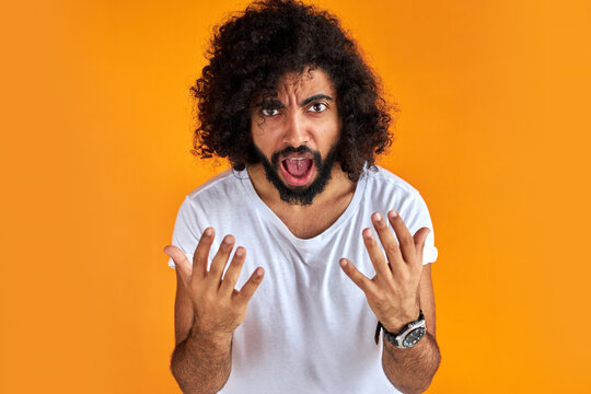 furious curly bearded man shout at someone, look at camera, he expresses aggression