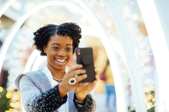 African American woman in a shopping center with a cell phone preparing for the holidays