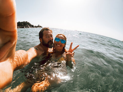 Cheerful adult couple take selfie picture swiming at the sea and enjoying summer holiday vacation together