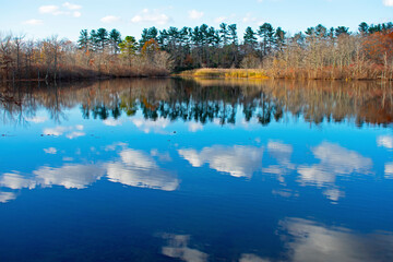Cumulus clouds and autumn foliage reflected in the calm waters of a small lake in East Brunswick, New Jersey, USA -02