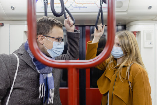 Flirty couple with covid 19 face masks in a train