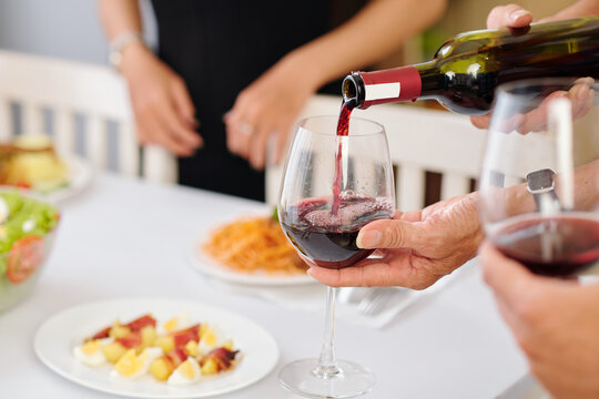 Person pouring red wine in glass for guest at house party