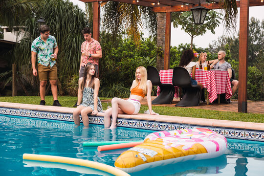 Friends enjoying the day at the pool and barbecue - Group of friends at a pool party.