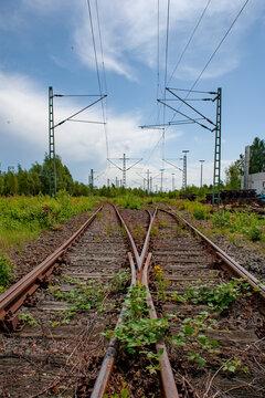 Stillgelegte Bahngleise und Weiche mit Hochspannungsleitung vor blauem Himmel