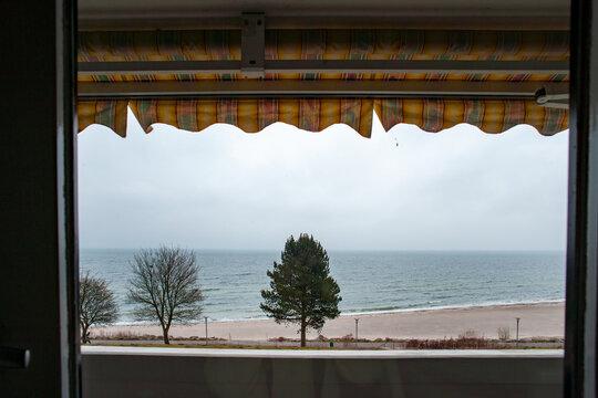 Blick unter Markise von Balkon auf den menschenleeren Strand der Ostsee