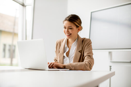 Young woman working on laptop in bright office with big screen behind her