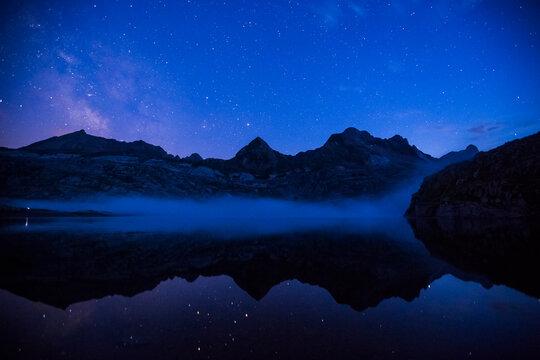 Summer night under Milky way in Ibon De Estanes lake, Aragon Pyrenees, Spain