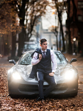 Successful businessman posing with luxury sports car holding the jacket suit at autumn city street