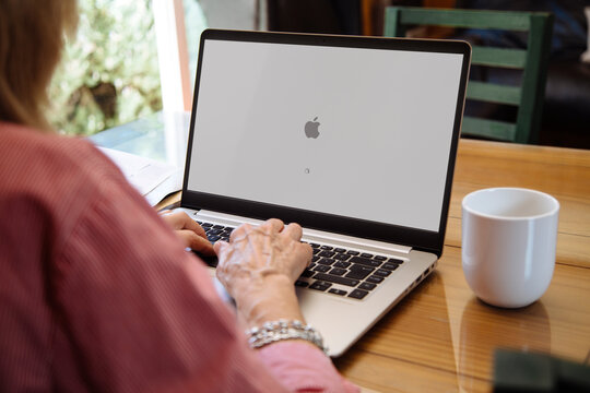 ROSARIO, ARGENTINA - NOVEMBER 16, 2020: Apple logo in the screen of laptop. Mature woman sitting in front of computer with mac os x operating system.
