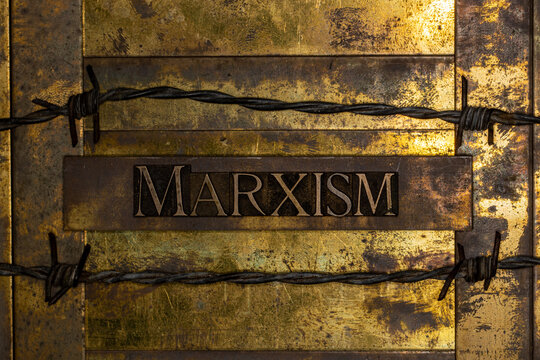 Marxism text on vintage textured grunge copper and gold background lined with barbed wire