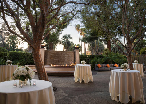 Tables dressed with linen in outdoor space for a reception