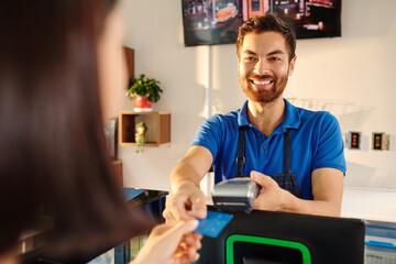 Happy smiling barista taking card of female customer to swipe it through terminal