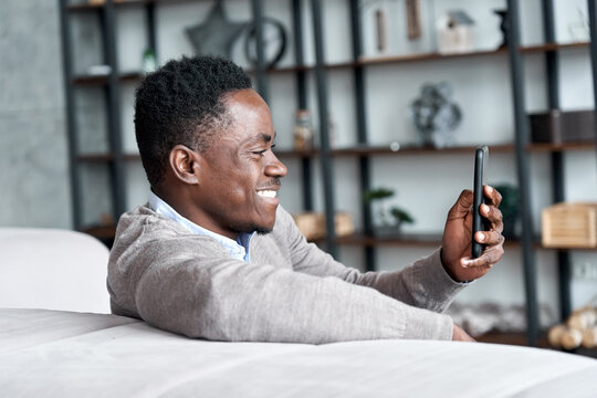Smiling african american man holding smart phone using social media apps sitting on couch at home. Black guy texting, remote learning, ordering distance delivery or chatting online in application.