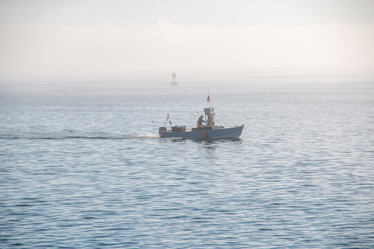 Fisherman's boat going across the ocean on a foggy day