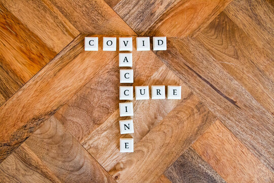 Letter blocks spelling out the words Covid, cure, and vaccine