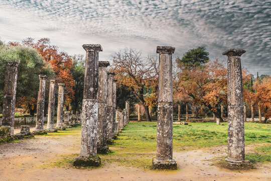 Pillars along pathway where atheletes used to run in acient Greece  in Olympia the site of the original Olympic games in winter under motled cloudy sky