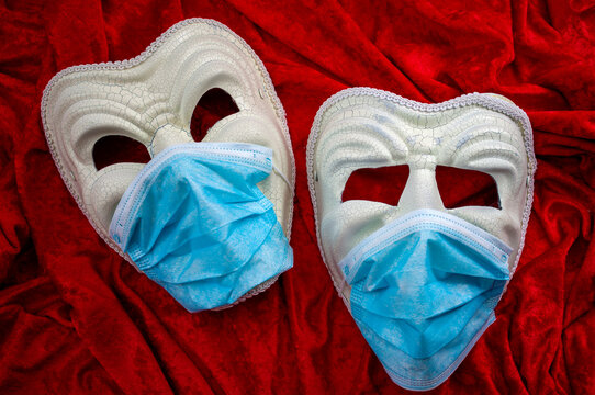 Coronavirus impact on theatre and the performing arts and the Covid-19 response is theater concept with the comedy mask and the one for tragedy wearing protection face masks on red velvet background