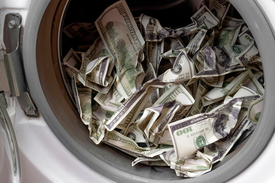Money laundering, financial fraud and whitewashing profits derived from crime and other illegal activities concept with close up on crumpled 100 dollar bill in washing machine