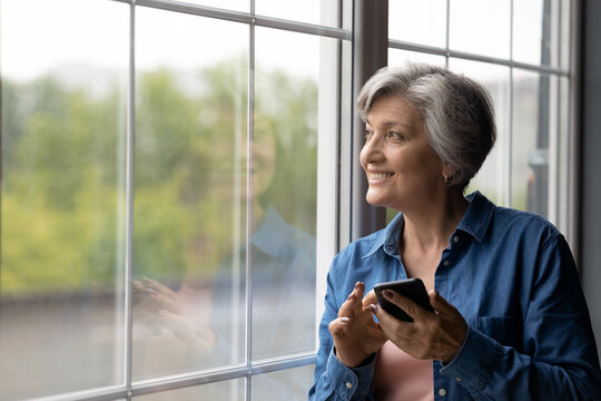 Smiling dreamy mature woman holding phone, looking out window close up, distracted from chatting online in social network, happy senior female waiting for call from relatives, enjoying leisure time