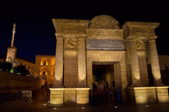 Puerta del Puente Roman Bridge Gate at night with Saint Raphael triumphal statue and Cordoba Cathedral Cordoba, Spain - May 2, 2015