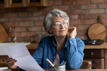 Dreamy smiling mature woman wearing glasses holding letter, reading news, thoughtful satisfied grey...