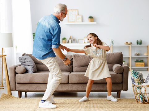 Grandfather dancing with granddaughter at home.