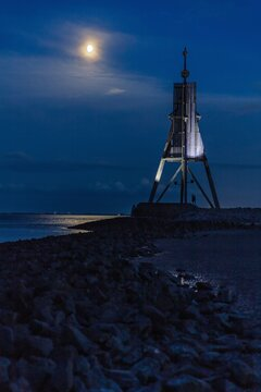 The 'Kugelbake', a historic aid to navigation in the city of Cuxhaven, Germany, at the northernmost point of Lower Saxony, where the River Elbe flows into the North Sea at nightfall.