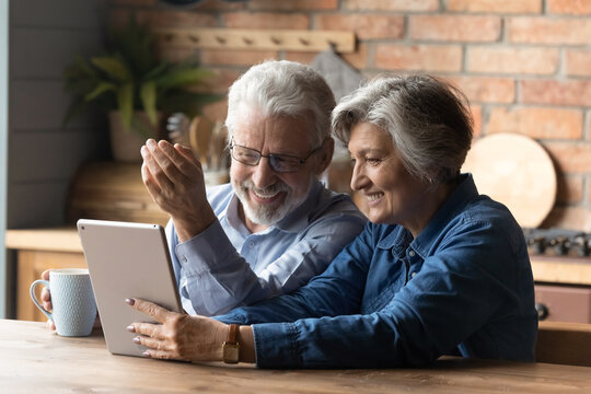 Happy mature couple having fun with tablet, sitting in kitchen, laughing senior man wearing glasses drinking tea or coffee in morning, grandparents chatting with relatives online, browsing apps