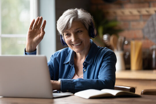 Close up smiling mature grey haired woman wearing headphones making video call, waving hand at webcam, greeting, chatting with relatives or friends, sitting at desk, looking at laptop screen