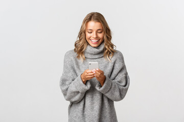 Portrait of young happy woman with short blond hair, using mobile phone and smiling, shopping...