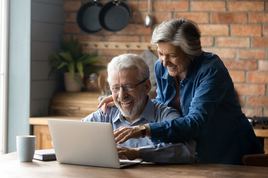 Overjoyed mature couple using laptop together, reading good news in email or message, shopping sales, smiling senior woman and man wearing glasses looking at screen, having fun with computer